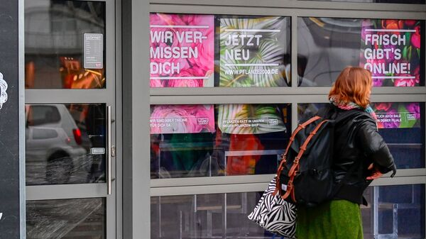 A woman walks past a closed flower shop in Berlin on Thursday. A research group noted more than 1,200 new words in German inspired by the pandemic.