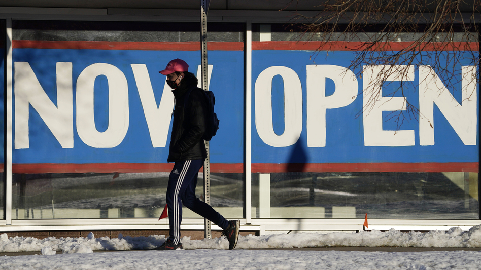 A pedestrian on Feb. 25 walks past the window of a restaurant with a sign promoting its re-opening in Boulder, Colo. Congress on Wednesday passed a $1.9 trillion stimulus plan, which is expected to provide a strong boost to economic growth. (David Zalubowski/AP)