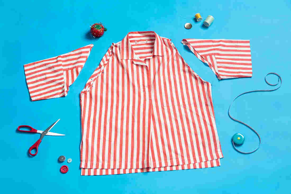 A red and white button-up shirt with the sleeves cut off and pinned lays on a bright blue background. The shirt is surrounded by scissors, a measuring tape, thread, buttons and a pin cushion.