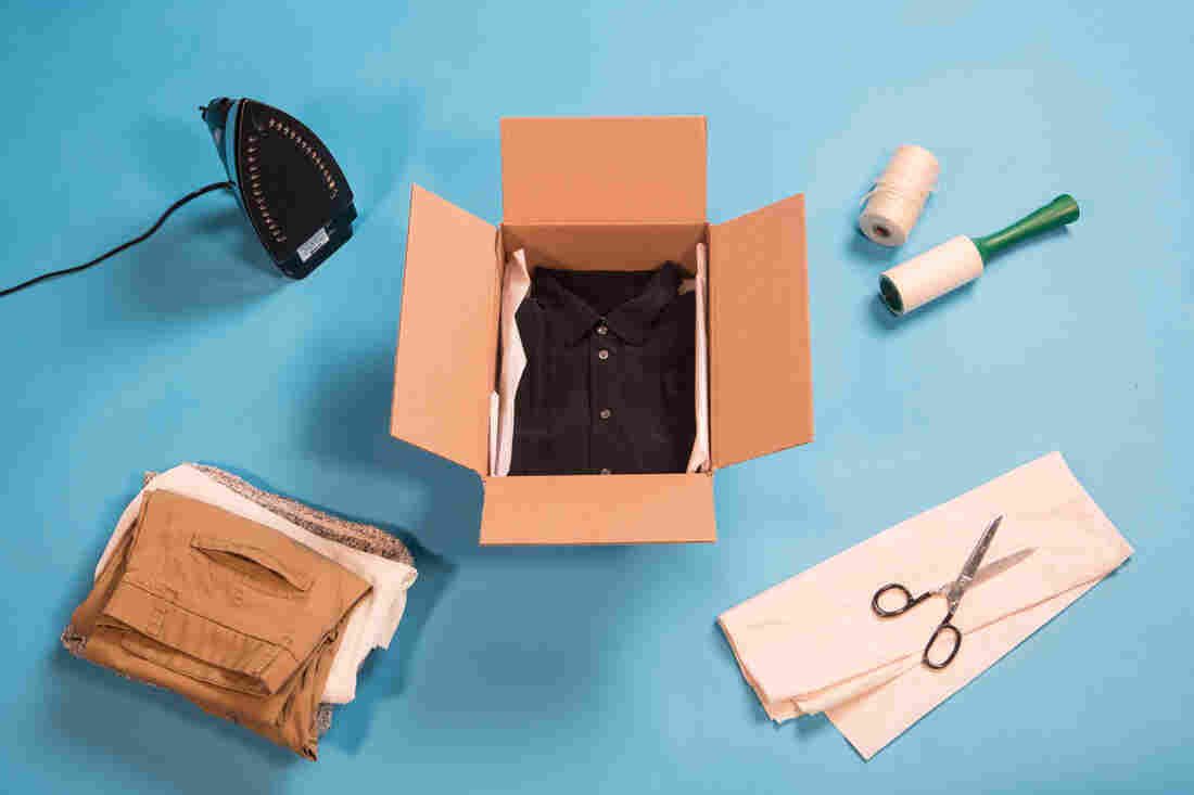 A black collared shirt is neatly folded inside a cardboard box on a blue background in the middle of the frame. The box is surrounded by an iron, a stack of clothes, a pair of scissors, tissue paper, twine and a lint roller.