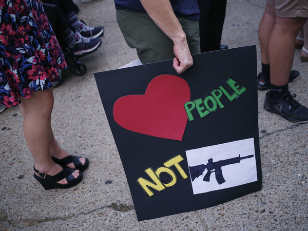 An activist holds a sign featuring an image of an assault weapon while demonstrating outside the office of Senate Majority Leader Mitch McConnell (R-KY) on August 6, 2019 in Louisville, Kentucky.