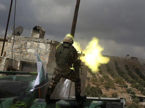 A fighter from Turkish-backed forces of the Free Syrian Army is shown in October 2019 firing a heavy machine gun during military training maneuvers in preparation for an anticipated Turkish incursion targeting Syrian Kurdish fighters, near Azaz, in north Syria.