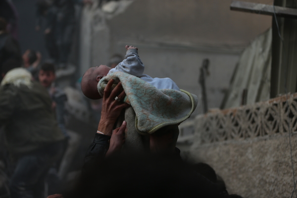 Jan. 7, 2014: Douma: A baby discovered in the rubble after an airstrike is lifted in the air.