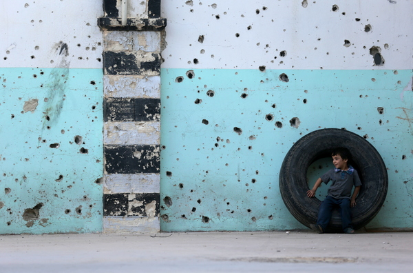 Oct. 4, 2014: Douma — A boy sits on a tire in front of a mosque's bullet-riddled facade on the first day of the Eid al-Adha holiday.