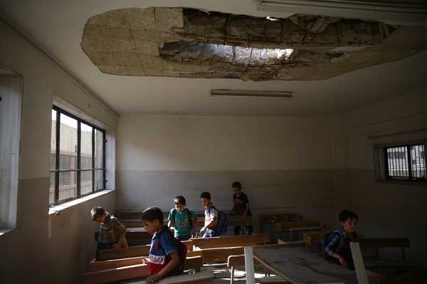 Sept. 16, 2017: Douma —  Students enter a damaged classroom on the first day of school. In this area, the start of school was postponed due to large-scale aerial bombardment. A number of parents and communities have created battlefield and underground schools in the hopes of preventing a generation of Syrians from growing up without education.