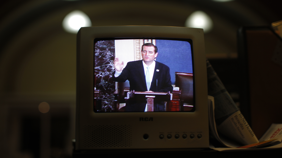 Seen on a TV in the Senate Press Gallery, Sen. Ted Cruz, R-Texas, speaks during the seventh hour of his 2013 filibuster in opposition to the Affordable Care Act. President Biden is advocating for a so-called talking filibuster. (Charles Dharapak/AP)