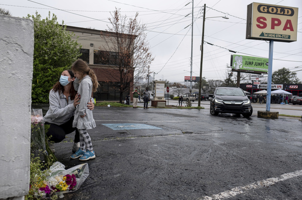 Mallory Rahman and her daughter Zara Rahman, 4, bring flowers to the Gold Spa massage parlor in Atlanta on Wednesday, the day after eight people were killed at three massage spas in the Atlanta area. Authorities have arrested Robert Aaron Long, 21, in the shootings at massage parlors in Atlanta and one in Cherokee County.