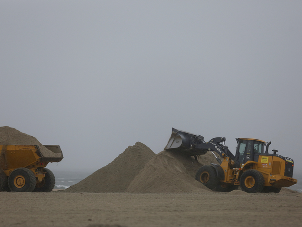 A front-end loader and dump truck move beach sand to protect vulnerable areas from flooding in in Southern California.