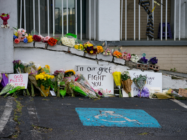 Flowers and signs adorn Gold Spa during a demonstration protesting violence against women and Asians following Tuesday night's shooting in the Atlanta area which killed eight.
