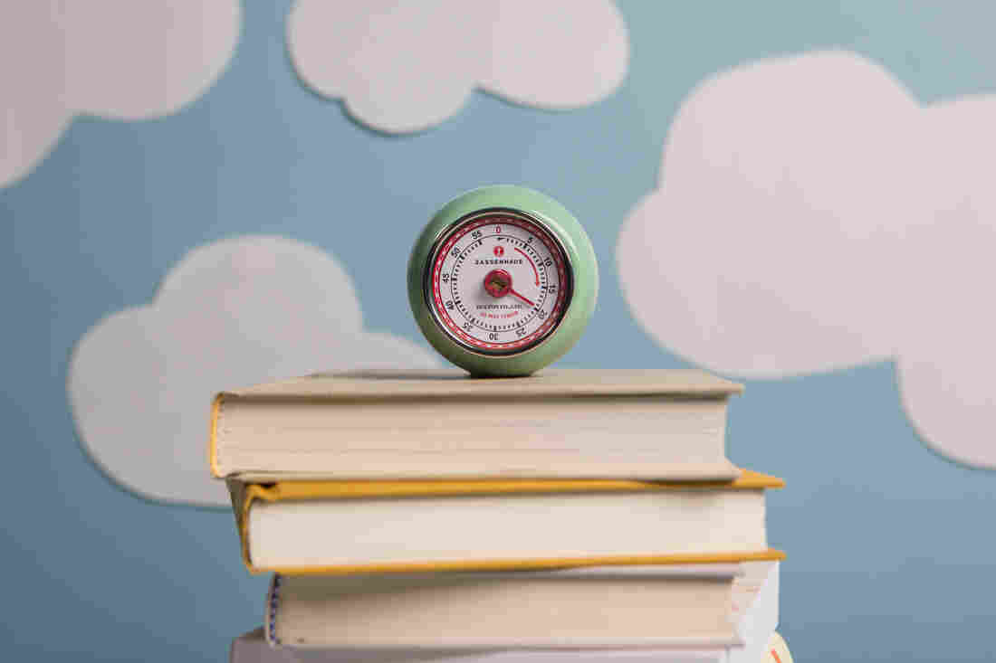 A sea-foam green egg timer set to 20 minutes sits atop a stack of closed books in front of a light blue backdrop covered in cutouts of white clouds.