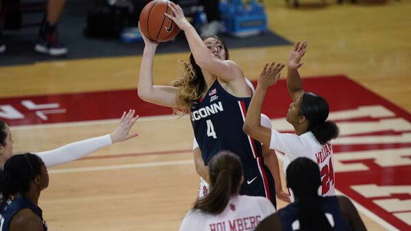 Connecticut guard Saylor Poffenbarger (4) is defended by St. John's guard Danaijah Williams (24) and forward Cecilia Holmberg (11) during the fourth quarter of an NCAA college basketball game in New York last month. The women's NCAA championship began on Sunday.