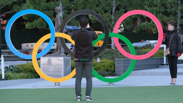 A couple takes pictures with the Olympic rings monument near the National Stadium for the Tokyo 2020 Olympic Games on Feb. 4. Organizers have decided that overseas spectators won't be allowed to attend the Games this summer.
