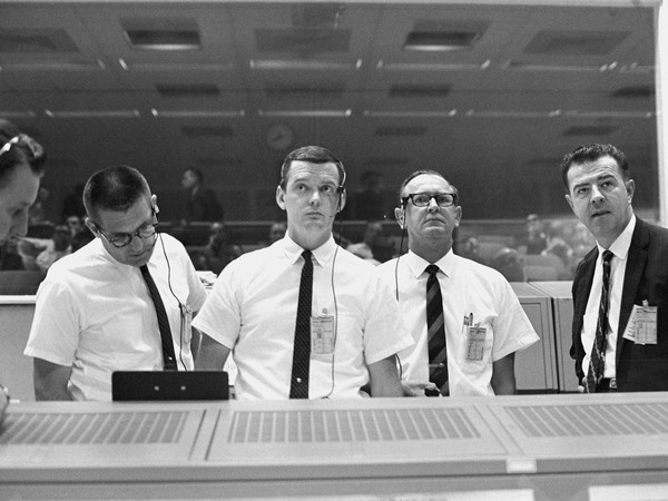 Viewing the Gemini 10 flight display in the Mission Control Center on July 18, 1966 are (from left) Mission Director William Schneider, Prime Flight Director Glynn Lunney, Flight Operations Director Christopher Kraft Jr. and Gemini Program Manager Charles Mathews.