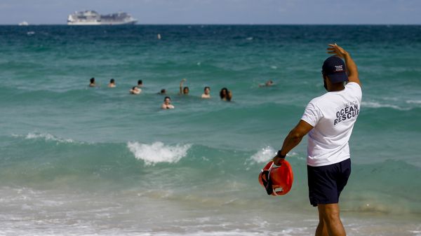 A lifeguard calls to swimmers at a beach in Miami on March 5. Amid fears of crowds fueling a new surge in coronavirus cases, Miami Beach on Saturday announced an abrupt curfew to curb swelling crowds of spring breaker visitors.