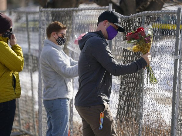 Kiefer Johnson places flowers Tuesday in a makeshift fence around the parking lot outside the King Soopers grocery store in Boulder, Colo., where 10 people were killed a day earlier.