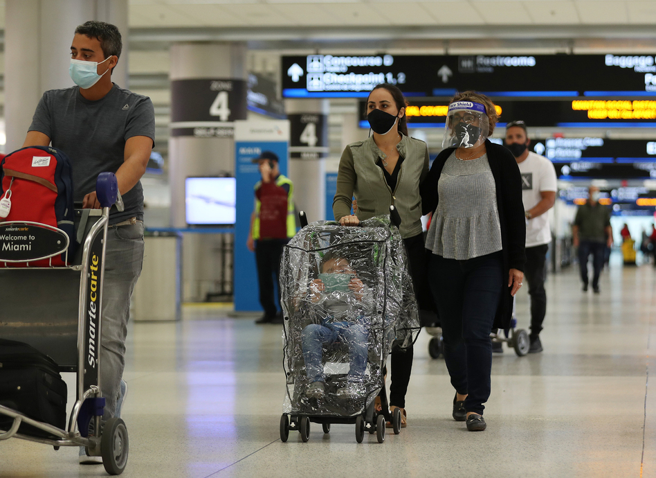 With precautions such as mask-wearing in place, experts predict travel is among the activities that may become safer by this summer. (Joe Raedle/Getty Images)