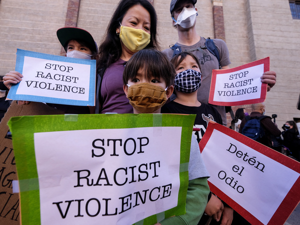 """A family wearing face masks and holding signs take part in a rally """"Love Our Communities: Build Collective Power"""" to raise awareness of anti-Asian violence, at the Japanese American National Museum in Little Tokyo in Los Angeles, California, on March 13."""