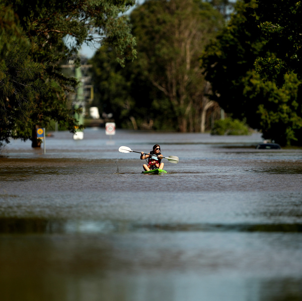 A local resident paddles along a flooded street in the Sydney suburb of McGraths Hill on Wednesday.