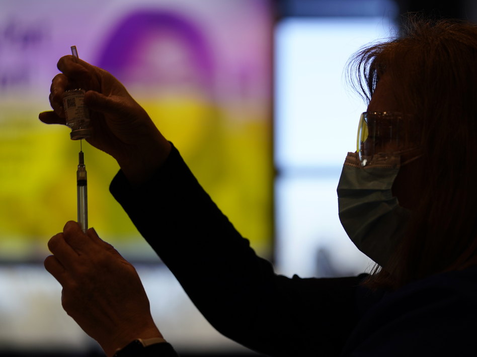 A county health worker fills a syringe with the Moderna COVID-19 vaccine in West Chester, Pa., in late December. Rutgers University will require students enrolling for the fall semester to show they have received a COVID-19 vaccine. (Matt Slocum/AP)