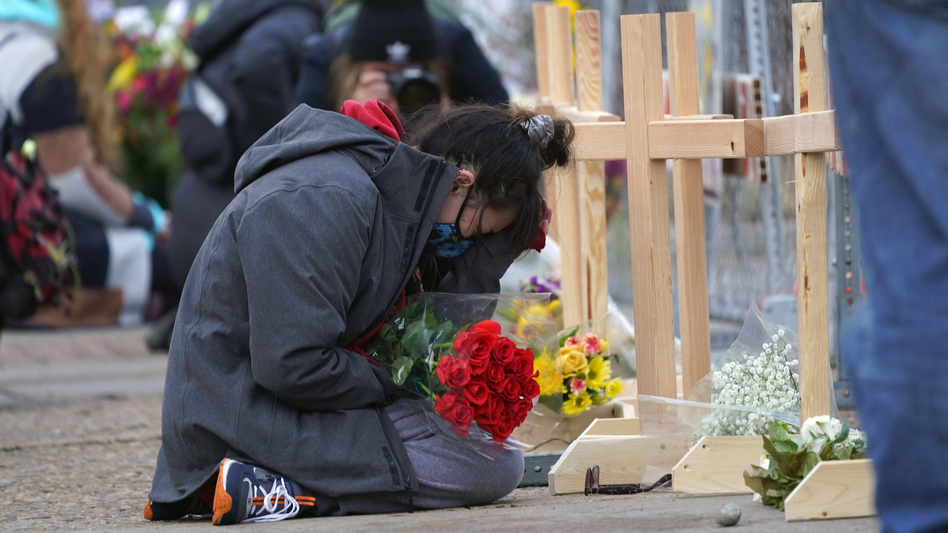 Star Samkus, who works at the King Soopers grocery store and knew three of the victims of a mass shooting at the store a day earlier, cries while kneeling in front of crosses placed in honor of the victims, Tuesday, March 23, 2021, in Boulder, Colo. (David Zalubowski/AP)