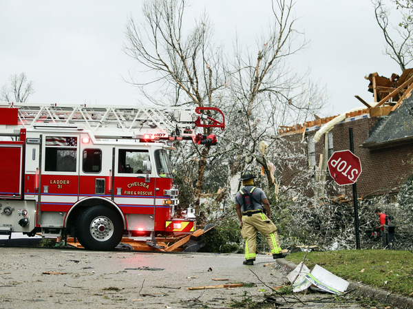"""A firefighter surveys damage after a tornado touches down south of Birmingham, Ala., in the Eagle Point community damaging multiple homes. The long-track """"super cell"""" storm has traveled in excess of 100 miles so far and this same system is still on the ground as it moves east and approaching Georgia."""