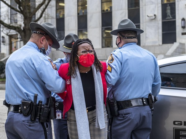 State Rep. Park Cannon is placed into the back of a Georgia State Capitol patrol car after being arrested at the Georgia State Capitol Building. Cannon was arrested after she attempted to knock on the door of the Gov. Brian Kemp office during his remarks after signing into law a sweeping Republican-sponsored overhaul of state elections.