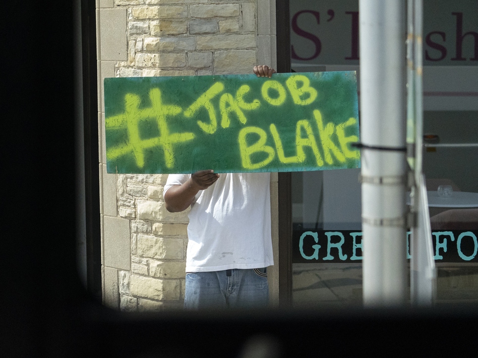 A Jacob Blake sign was on display as the motorcade of then-presidential candidate Joe Biden passed by in Kenosha Wis., on Sept. 3, 2020. A team of attorneys representing Blake have filed an excessive force lawsuit against the officer who shot and paralyzed him in August. (Carolyn Kaster/AP)