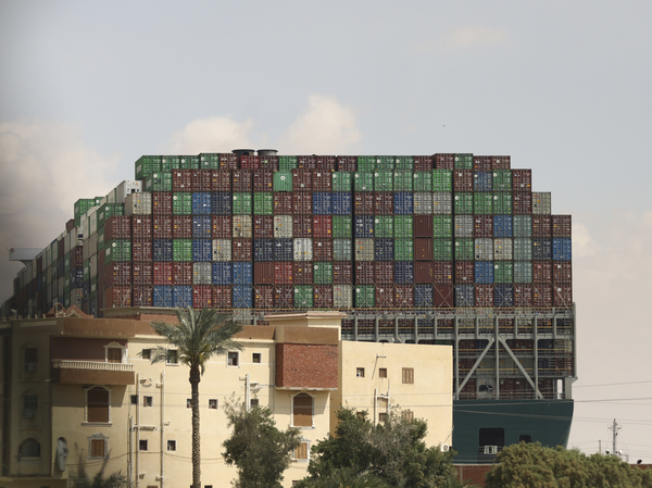 The Panama-flagged Ever Given is seen wedged across the Suez Canal on Friday. Tugboats, dredgers and even land-based earth-moving equipment have been pressed into service to try to free the 1,300-foot container ship.