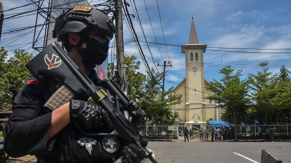A police officer stands guard outside the Sacred Heart of Jesus Cathedral in Makassar, Indonesia, on Sunday. Two suicide bombers attacked the Roman Catholic compound, injuring at least 20 people. (Indra Abriyanto/AFP via Getty Images)