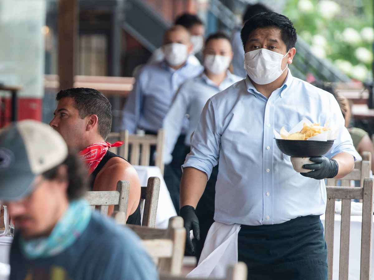 A waiter wearing a mask and gloves delivers food to a table to customers seated at an outdoor patio at a Mexican restaurant in Washington, DC, May 29, 2020.