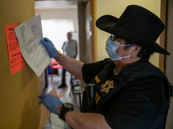 A Maricopa County constable posts an eviction order for non-payment of rent in October in Phoenix, Arizona. The Centers for Disease Control (CDC) is extending an order aimed at preventing evictions. That should protect many people, but thousands of court-ordered evictions continue nationwide due to loopholes in the CDC moratorium.