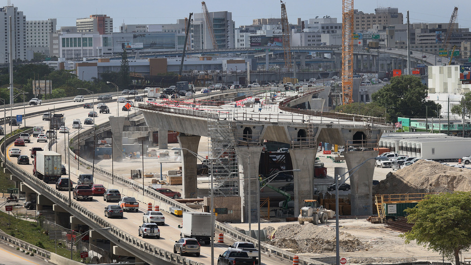 Workers improve a busy highway intersection in Miami. President Biden is proposing roughly $2 trillion to invest in the nation's infrastructure. His plan includes improvements for roads, bridges, transit, water systems, electric grids and Internet access. (Joe Raedle/Getty Images)