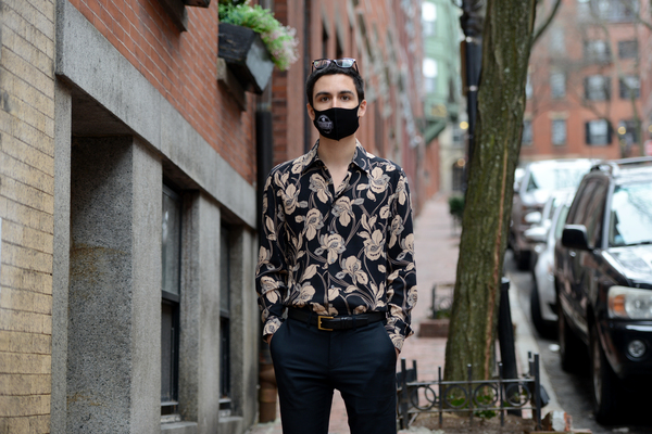 Gabriel Toro, 23, stands on the sidewalk near his apartment in Boston on March 11. Toro completed the credits required for a bachelor's degree from the University of Massachusetts Boston but the school wouldn't release Toro's transcript or degree because of an unpaid balance.