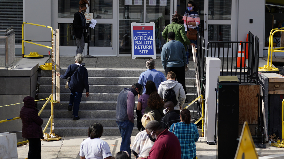 Residents line up outside the Montgomery County voter services office in October in Norristown, Pa. Last year, Joe Biden ran up the vote margins in the collar counties of Philadelphia, including Montgomery. (Matt Slocum/AP)