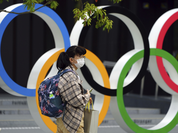 A woman wearing a protective mask to help curb the spread of the coronavirus walks in front of he Olympic Rings on Tuesday in Tokyo. North Korea says it will not attend the games over COVID-19 fears.