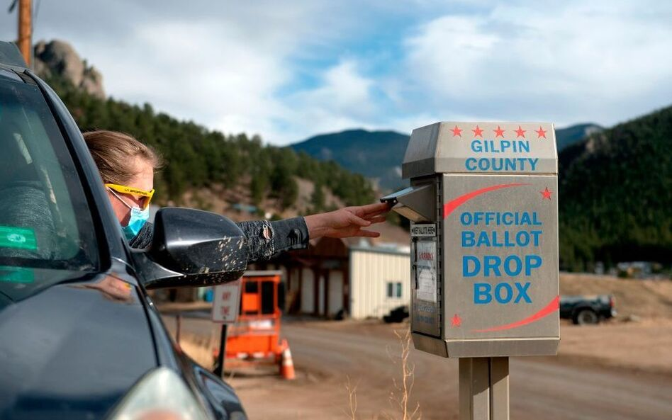 A voter drops off her ballot for the U.S. presidential election in November, in Rollinsville, Colo. Colorado's voting laws got fresh attention this week after the MLB decided to move its All-Star game to the state to protest Georgia's new legislation. (Jason Connolly/AFP via Getty Images)