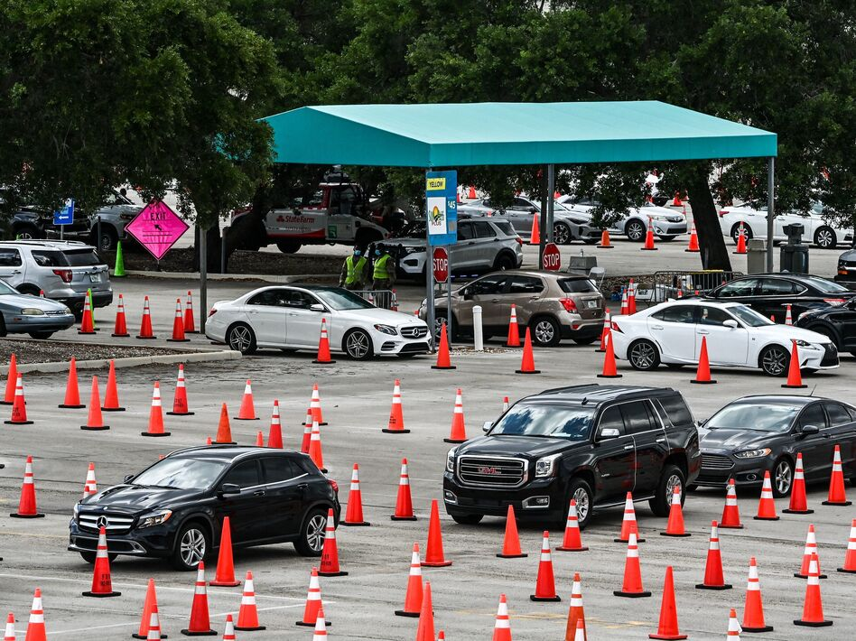 People wait in their vehicles to get vaccinated last week at a drive-through site at Hard Rock Stadium in Miami Gardens, Fla. President Biden announced an April 19 deadline for all states to open eligibility to individuals ages 18 and up. (Chandan Khanna/AFP via Getty Images)