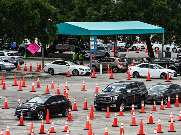 People wait in their vehicles to get vaccinated last week at a drive-through site at Hard Rock Stadium in Miami Gardens, Fla. President Biden is expected to announce an April 19 deadline for all states to open eligibility to individuals ages 16 and up.