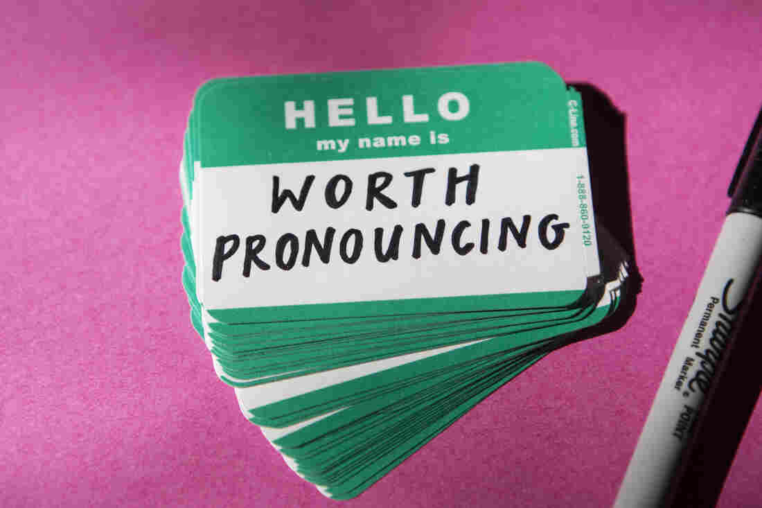 """A teal name tag that reads """"Hello my name is"""" is filled out """"worth pronouncing."""" The name tag sits on a stack of other name tags against a magenta background."""