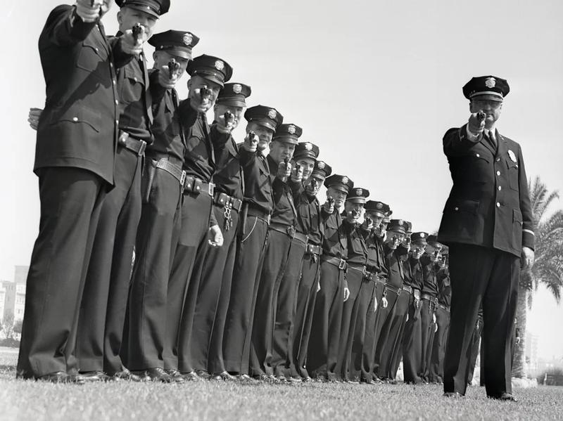 A line of policeman take aim.