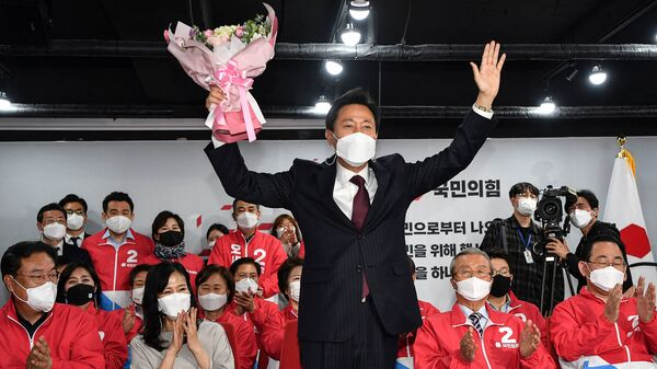 Oh Se-hoon, center, the mayoral candidate of the main opposition People Power Party, holds flowers as he celebrates with party members after exit polls showed he would win.
