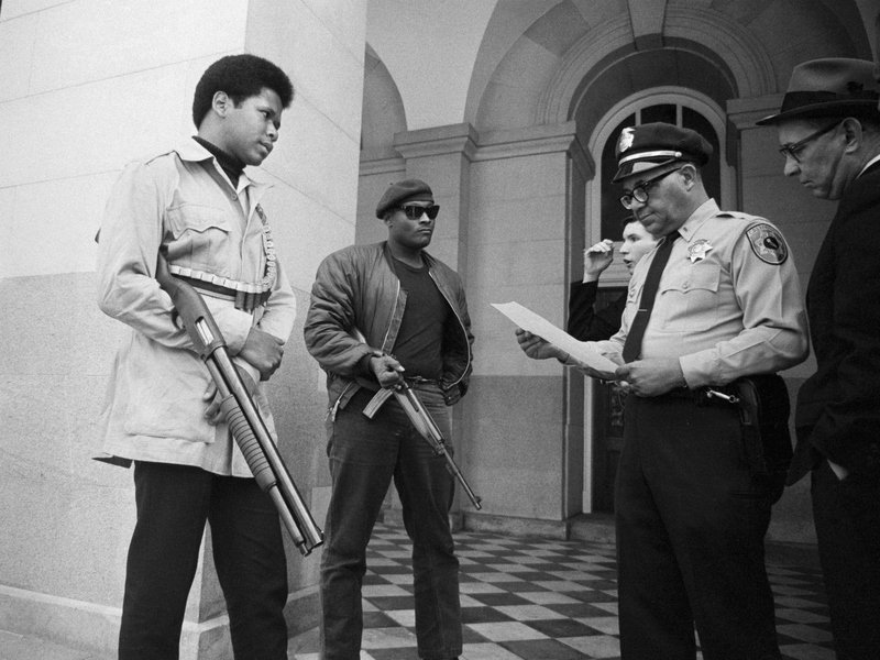 Two members of the Black Panther Party are met on the steps of the State Capitol in Sacramento, California in 1967
