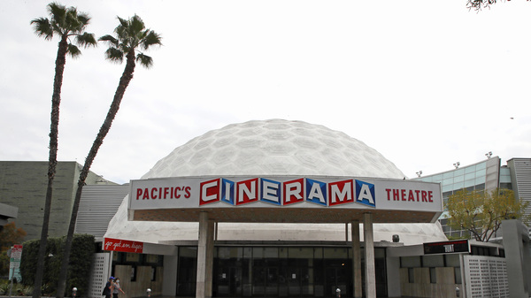 People wearing protective face masks walk by the closed Cinerama Dome theater during the coronavirus pandemic on April 18, 2020 in Los Angeles, Calif.