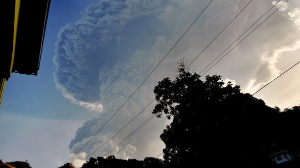 An ash plume rises over La Soufriere on St. Vincent on April 13. The volcano is expected to continue erupting and has caused a humanitarian crisis.