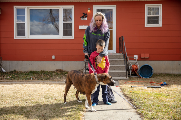 Barbara Gaught stands outside the home she's now renting in Billings, Mont., with her five-year-old son Blazen and their dog Arie on March 27, 2021. Gaught and her family were evicted from the mobile home they had owned outright and lived in for 16 years because they fell behind on 'lot rent' for the little plot of land under the mobile home.