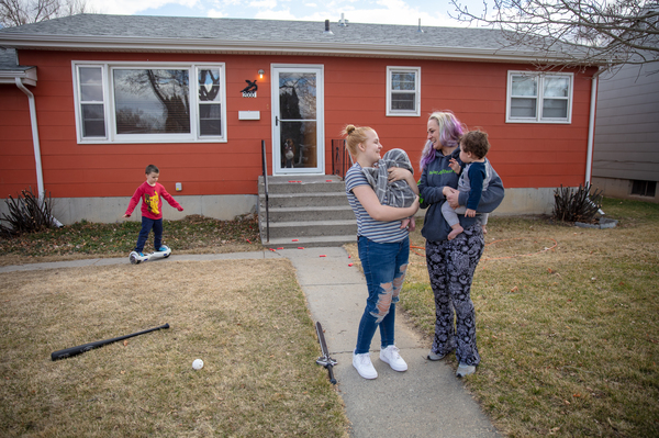 """Gaught (right) holds her 9-month-old grandson, Adonis, while her daughter Trinity, 16, holds her newborn baby at the home they now rent in Billings, Mont. Gaught's 5-year-old son, Blazen, plays in the background. She says out of all of them, Blazen has been most upset about losing the house. """"It's hard to explain to him why his home's not his home anymore,"""" Gaught says."""