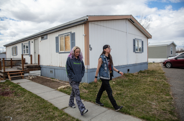 Gaught and her son, Izaah, check on their old home for notices left on the door. Gaught and her family were evicted from the home in a mobile home park in Billings, Mont., owned by Havenpark Communities. The company filed an eviction case against her in November after she fell one month behind on the rent and owed just $621.