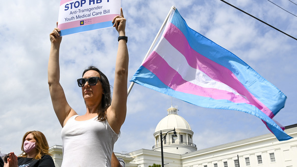 Sydney Duncan holds a sign during a rally at the Alabama State House to draw attention to legislation introduced in Alabama that's aimed at restricting transgender people's access to medical care.