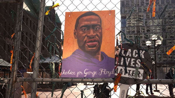 A picture of George Floyd hangs on a fence barrier that surrounds the Hennepin County Government Center in Minneapolis on March 30. The Justice Department is bringing criminal charges against former police officer Derek Chauvin for allegedly violating Floyd