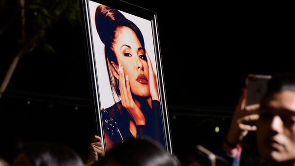 Fans with a photo of Selena during a ceremony honoring her in 2017. Over the decades since her death, Selena